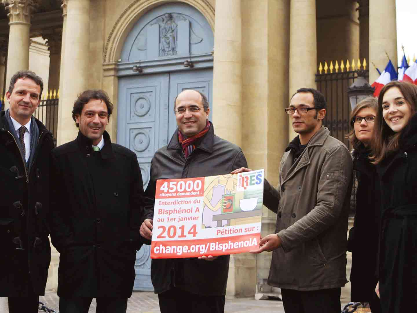 A group of supporters holding a sign in front of the French Senate.